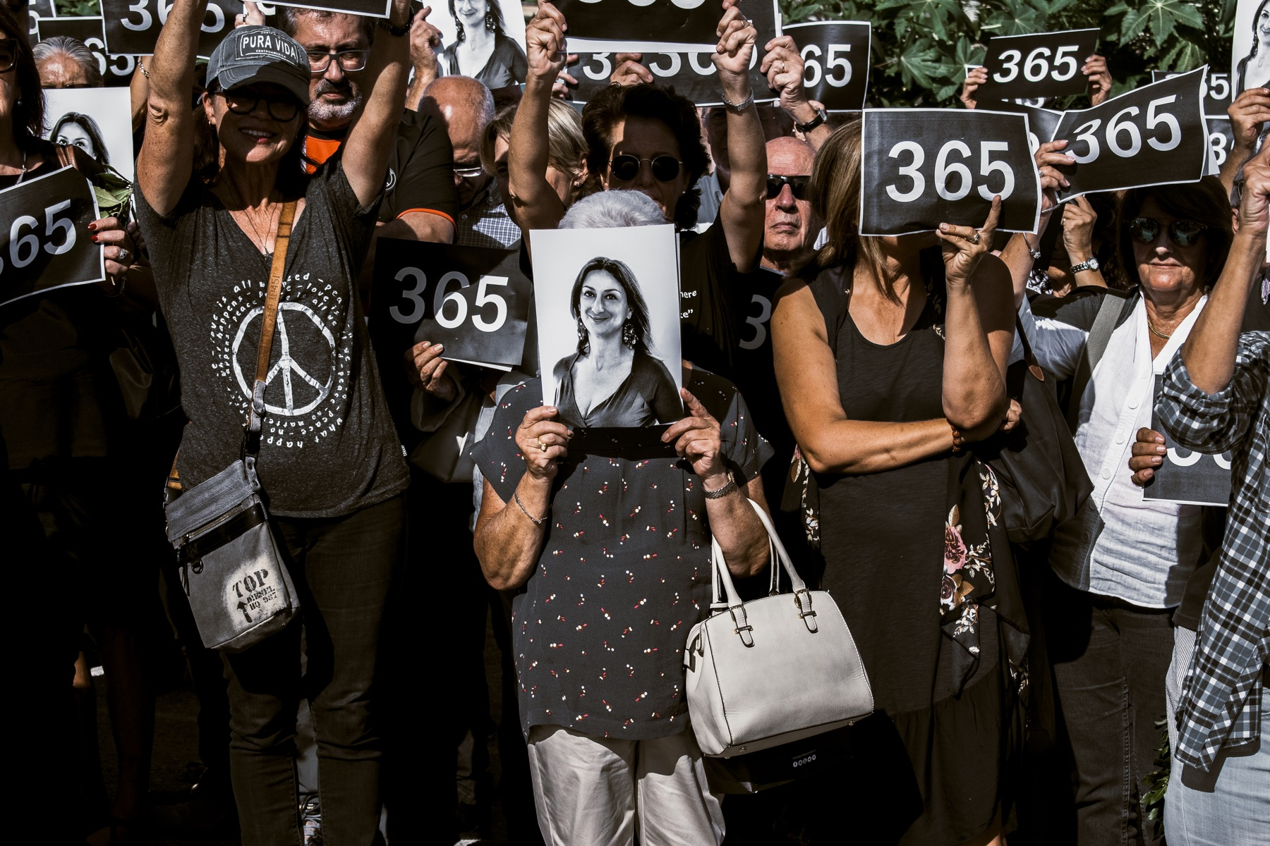 Protestors hold up photos of Daphne Caruana Galizia during a march on the first anniversary of her assassination.